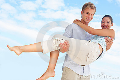 Handsome young man carrying his pretty girlfriend