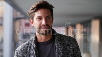 Handsome young man in city talking to camera. One handsome young man in urban setting in European city, standing, smiling and talking to the camera stock video footage
