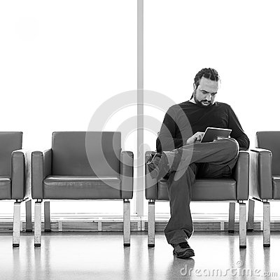 Handsome young man with dreadlocks using his digital tablet pc at an airport lounge, modern waiting room, with backlight
