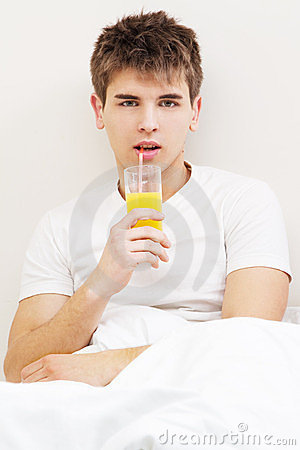 Handsome young man drinking juice