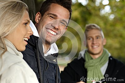 Handsome young man and friends in park smiling