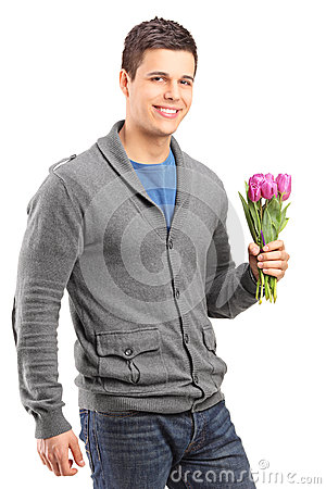 Handsome young man holding tulips