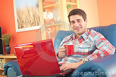 Handsome young man with laptop and coffee cup