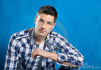 Handsome young man with plaid shirt on blue