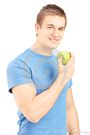Handsome young man posing with a green apple in his hand