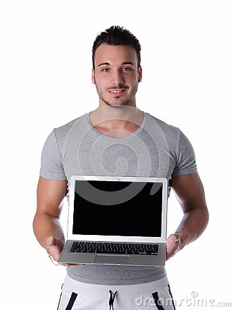 Handsome young man smiling and showing laptop computer