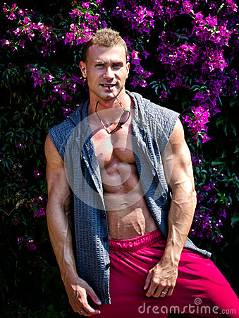 Handsome young muscle man smiling, outdoors, with open shirt