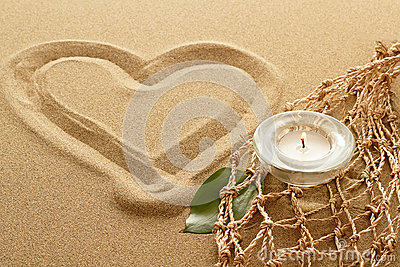 Handwritten heart on sand with lighted candles