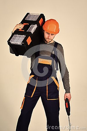 Free Handyman Concept. Man In Overall And Helmet Holds Toolbox On Shoulder And Drill In Hand. Strong And Attractive Repairer Stock Photos - 116680243