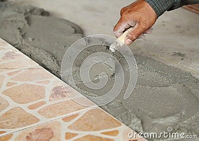 Handyman laying tile, trowel with mortar