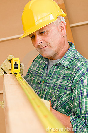 Handyman mature carpenter measure wooden beam
