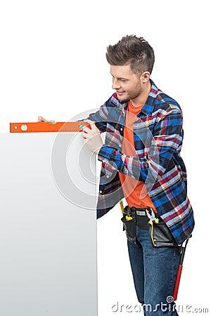 Handyman measuring level.