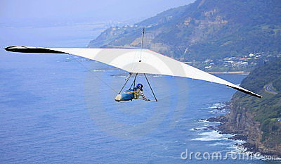 Hang glider flying over the ocean