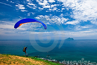 Hang glider in sky over blue sea