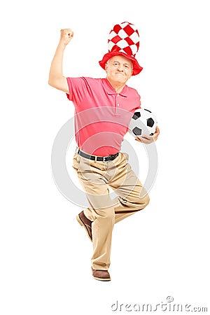 中部变老了与拿着球和打手势happ的帽子的体育迷