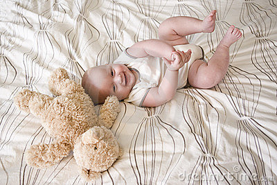 Happy 7 month old baby lying next to teddy bear