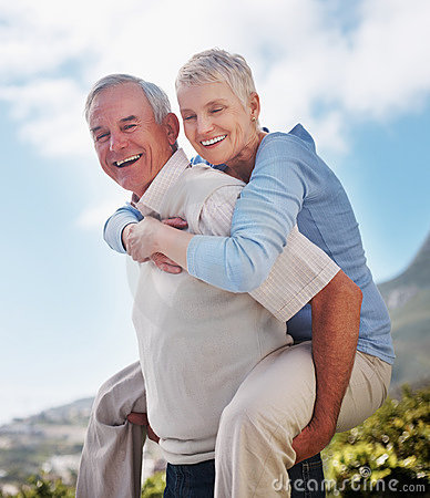 Happy active older man giving woman piggyback ride