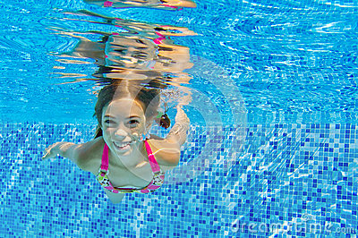 Happy active underwater child swims and dives in pool