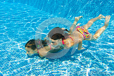 Happy active underwater children swim in pool