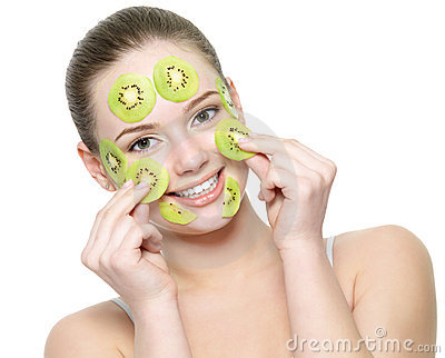 Happy adult woman with kiwi facial mask
