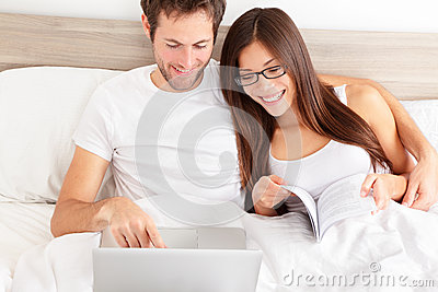 Happy affectionate couple laughing at their laptop