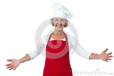 Happy aged chef gesturing welcome