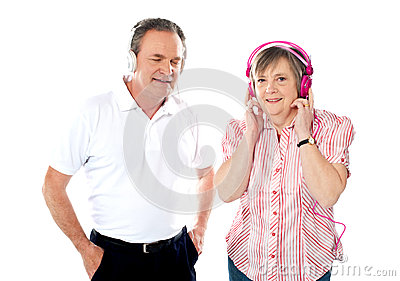 Happy aged couple enjoying music together