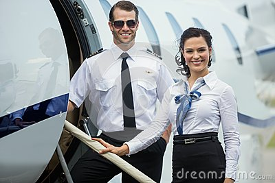 Happy Airhostess And Pilot Standing On Private