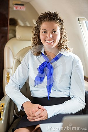 Happy Airhostess Sitting In Private Jet