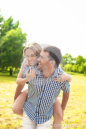 Free Happy And Cheerful Young Caucasian Couple Piggybacking Outdoors. Stock Photography - 49809442