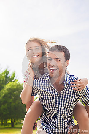Free Happy And Cheerful Young Caucasian Couple Piggybacking Outdoors. Royalty Free Stock Photography - 50385197