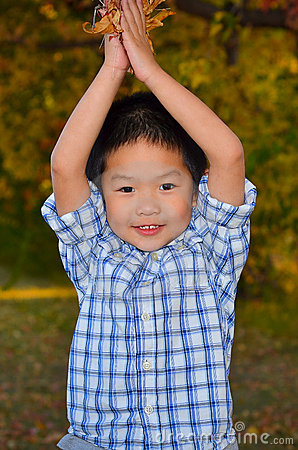 Happy Asian Boy Playing With Autumn Leaves