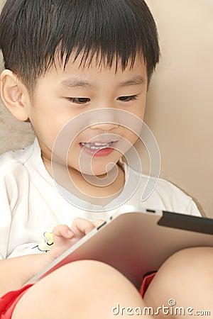 Happy Asian boy playing iPad
