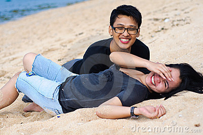 Happy asian couple lying down at beach
