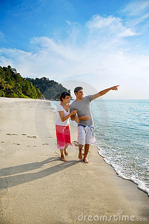 Happy asian couple walking along the beach