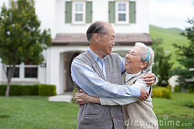 Happy Asian Elderly Couple in front Yard
