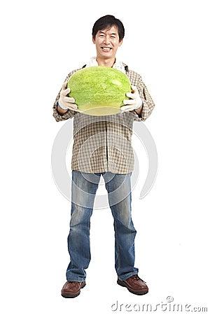 Happy asian farmer holding watermelon