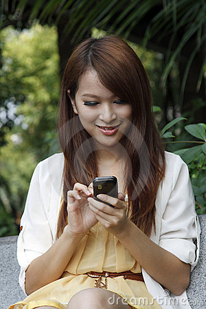 Happy asian girl using mobile phone