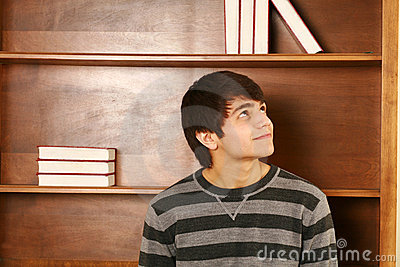 Happy asian man in front of book shelf
