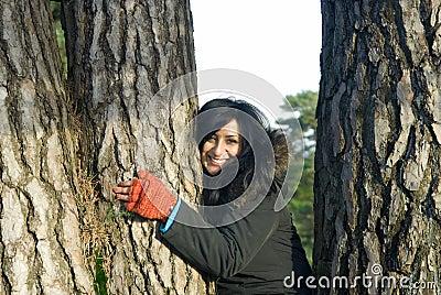 Happy Asian woman hugging a tree