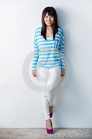 Happy Asian woman leaning against wall.