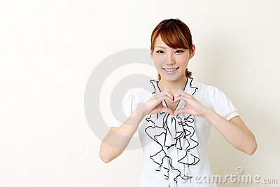 Happy asian woman make heart shape by her hands