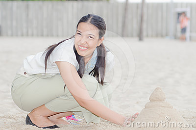 Happy Asian Woman play Castle Sand
