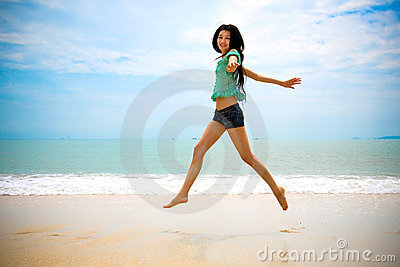 Happy asian woman walking in the air at the beach