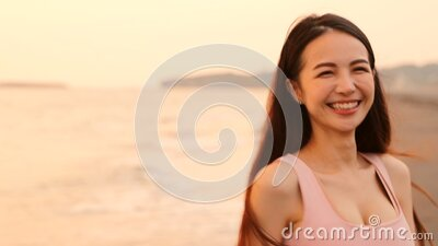 Happy asian young woman walking on the beach at sunset stock video footage