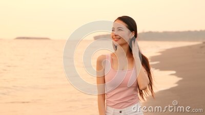 Happy asian young woman walking on the beach at sunset stock footage