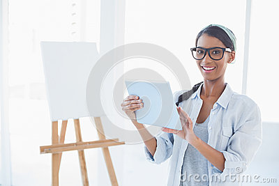 Happy attractive artist using her tablet pc