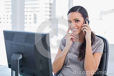 Happy attractive businesswoman having a phone conversation