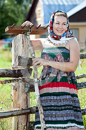 Happy attractive country girl in sundress and headscarf against house