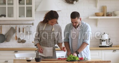 Happy attractive woman feeding husband while cooking together. Happy attractive woman feeding husband while cooking together at modern kitchen. Smiling family stock footage